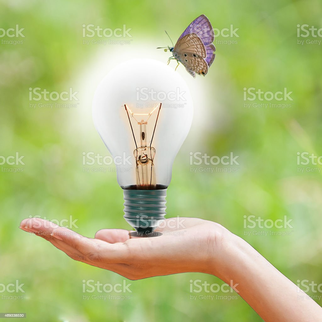hand holding a light bulb on green bokeh background stock photo