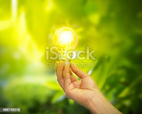 hand holding a light bulb with energy on fresh green nature background, soft focus