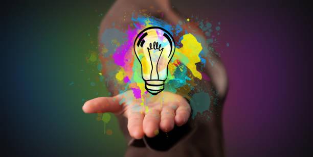 Hand holding a lighting bulb stock photo