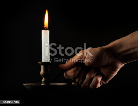 Holding a candleholder in the dark. Skin texture clearly visible.