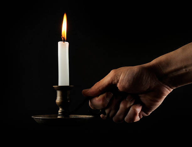 hand holding a lit candle in the dark - kandelaar stockfoto's en -beelden