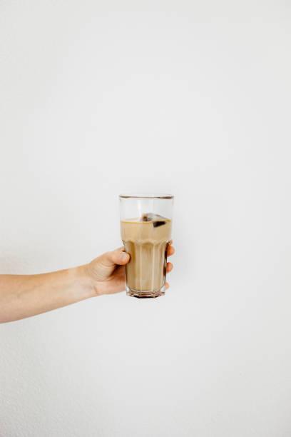 hand hält eine lange glas mit eiskaffee. kaffee-eiswürfel gegossen mit milch eingefroren. weißer hintergrund, isoliert, raum zu kopieren. - hausgemachter eiskaffee stock-fotos und bilder