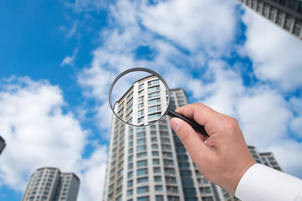 A hand holding a magnifying glass against the backdrop of an apartment. stock photo