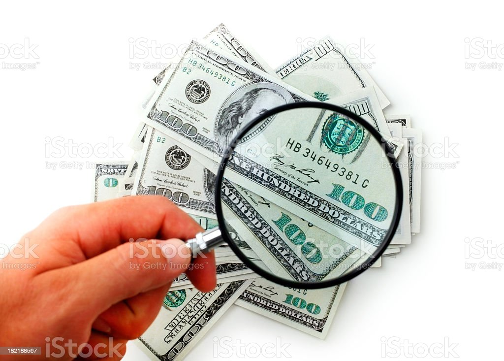 Hand holding a magnifying glass over US dollars royalty-free stock photo