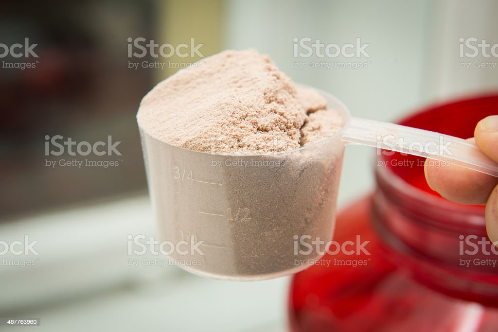 Hand holding a measuring scoop filled with whey protein stock photo