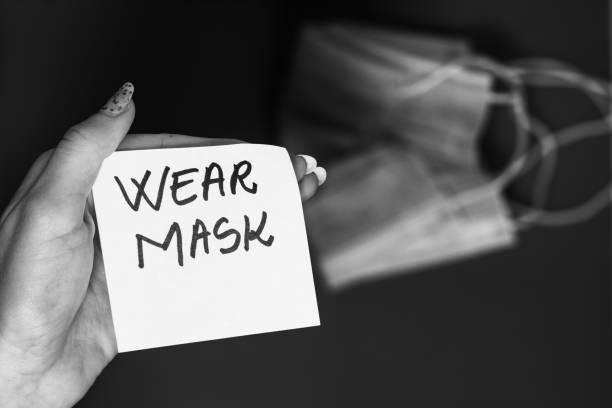 Hand hält eine Memo-Post-Erinnerung mit Text tragen Maske isoliert auf verschwommenen Hintergrund mit chirurgischen Maske. Ausbreitung des Grippevirus in Europa, Methoden zum Schutz von Viren. – Foto