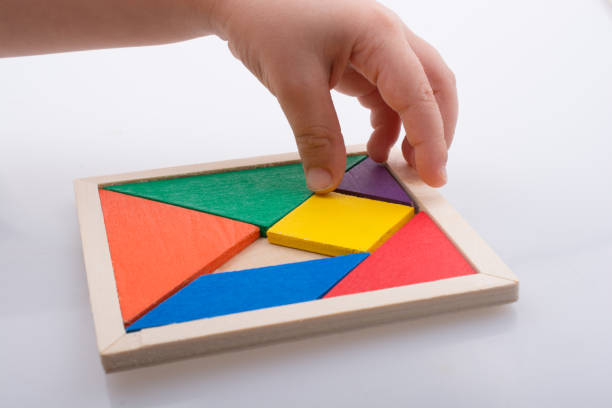 hand holding a missing piece in a tangram puzzle stock photo