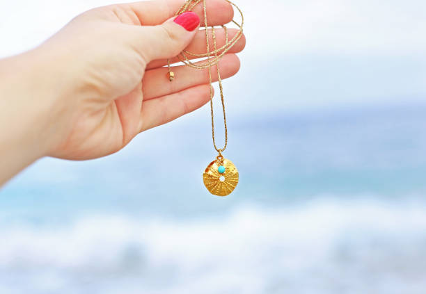 hand holding a necklace with a golden sea urchin and turquoise stone in front of the sea stock photo