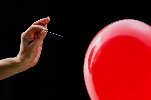 Hand holding a needle next to a red balloon
