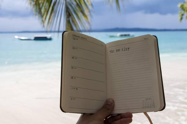 hand met een notitie pad op het strand met takenlijst - newspaper beach stockfoto's en -beelden