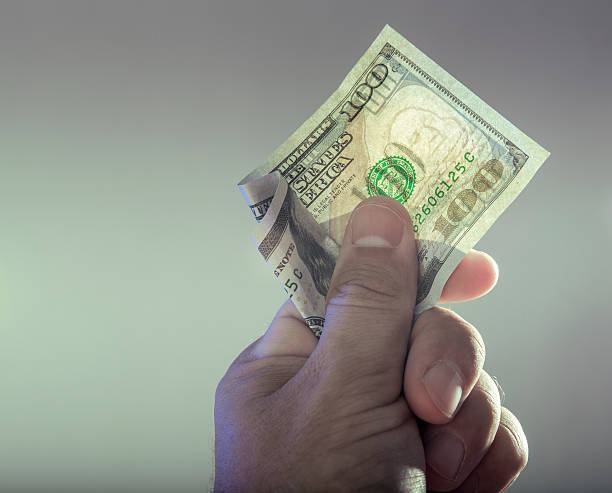 hand holding a one hundred dollar bill - watermark stock photos and pictures