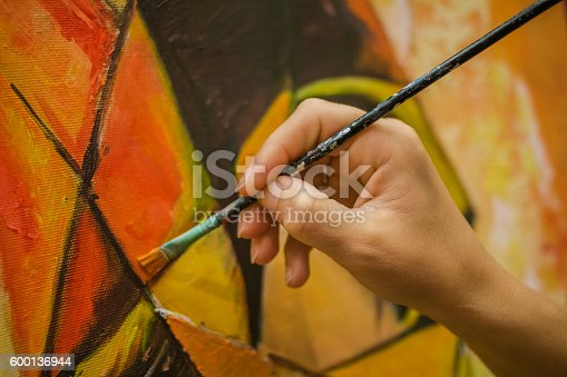 istock Hand holding a paintbrush 600136944