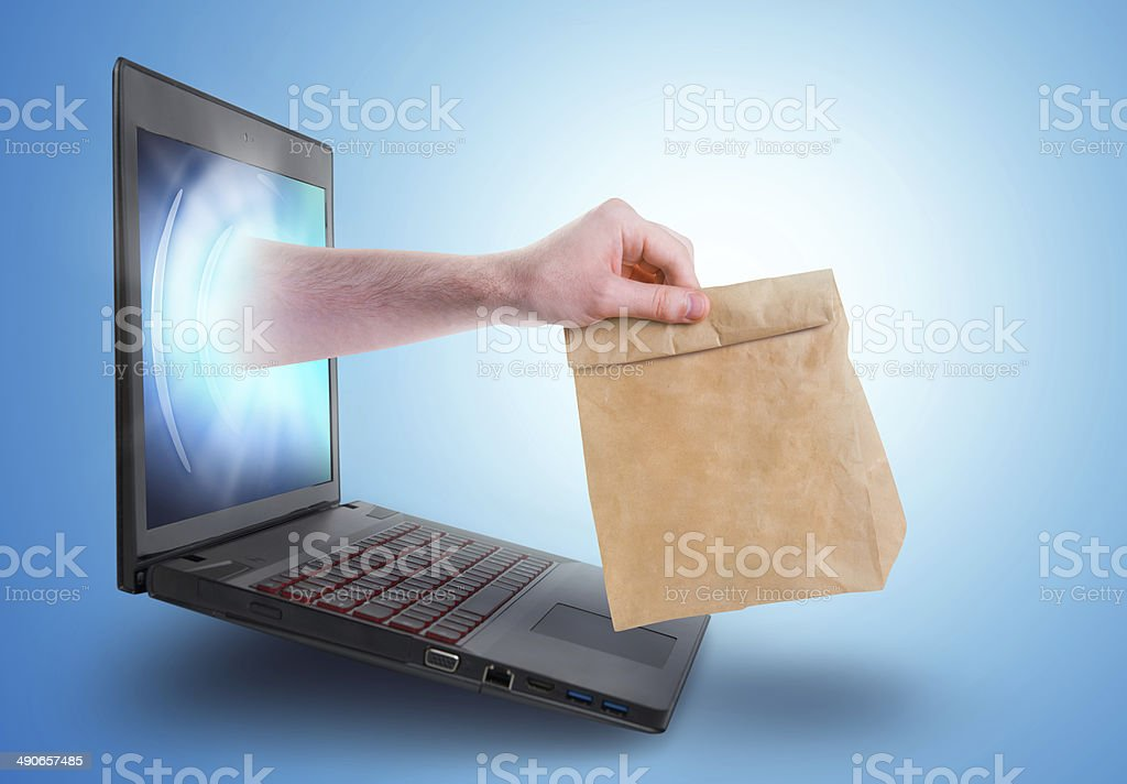Hand holding a paper bag coming out of laptop screen stock photo