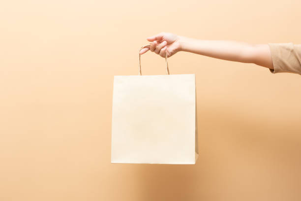 Hand holding a paper bag isolated on background stock photo