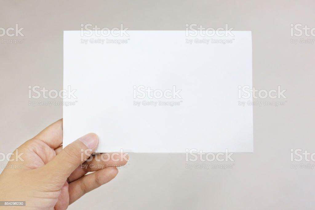 Une main tenant une carte de papier photo libre de droits