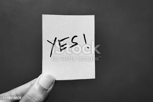 Hand holding a paper card with the word YES