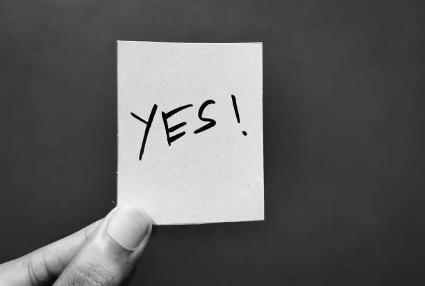 Hand holding a paper card with the word YES Hand holding a paper card with the word YES yes single word stock pictures, royalty-free photos & images