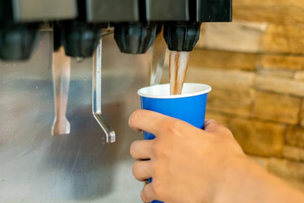 hand hält ein papierglas, um die limonade soda softdrink-maschine in einem fastfood-restaurant zu gießen - alkoholfreies getränk stock-fotos und bilder
