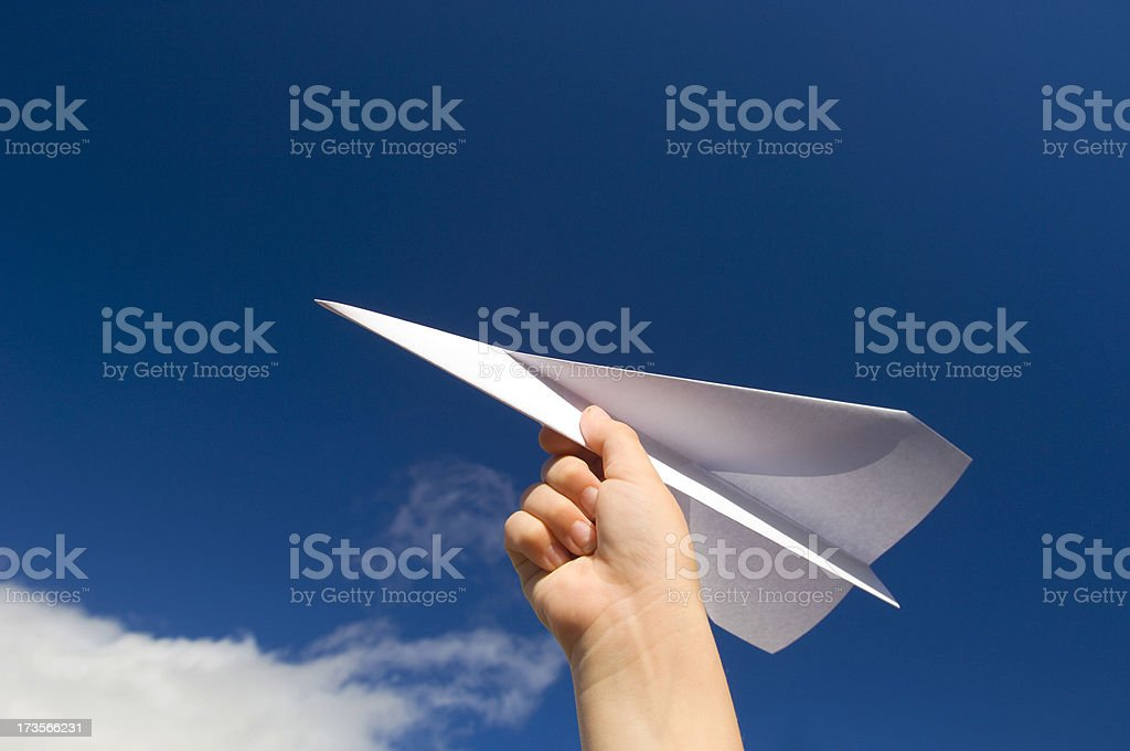 A hand holding a paper plane with the view of the sky stock photo