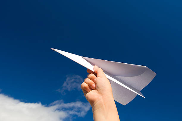 a hand holding a paper plane with the view of the sky - paper airplane stock photos and pictures