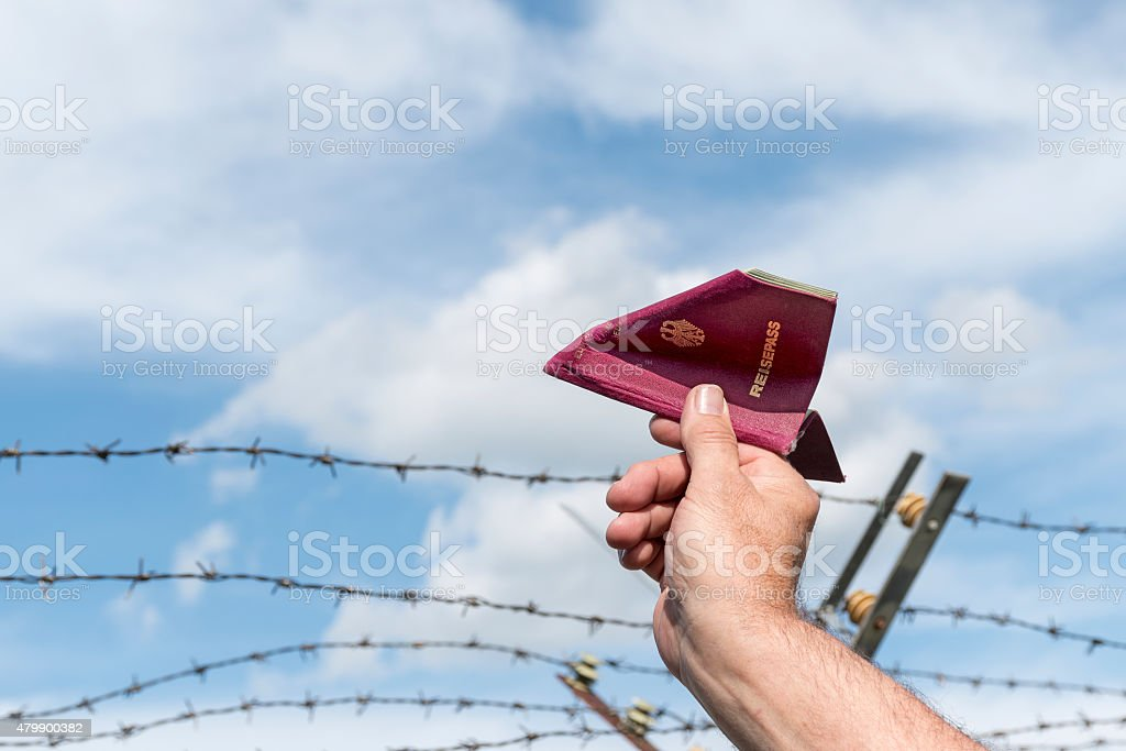 hand holding a passport like a paper airplane stock photo