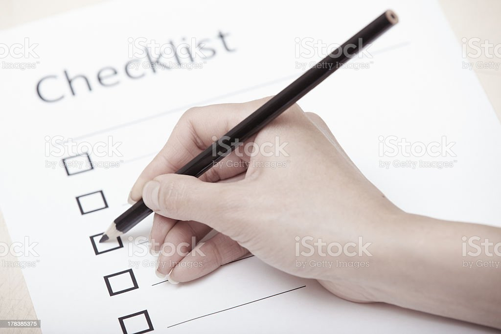 Hand holding a pencil while completing a checklist royalty-free stock photo
