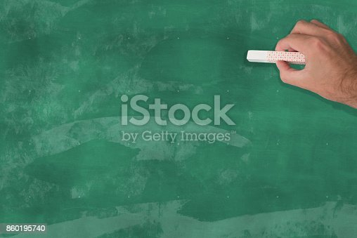 istock hand holding a piece of chalk in front of a blank chalkboard 860195740