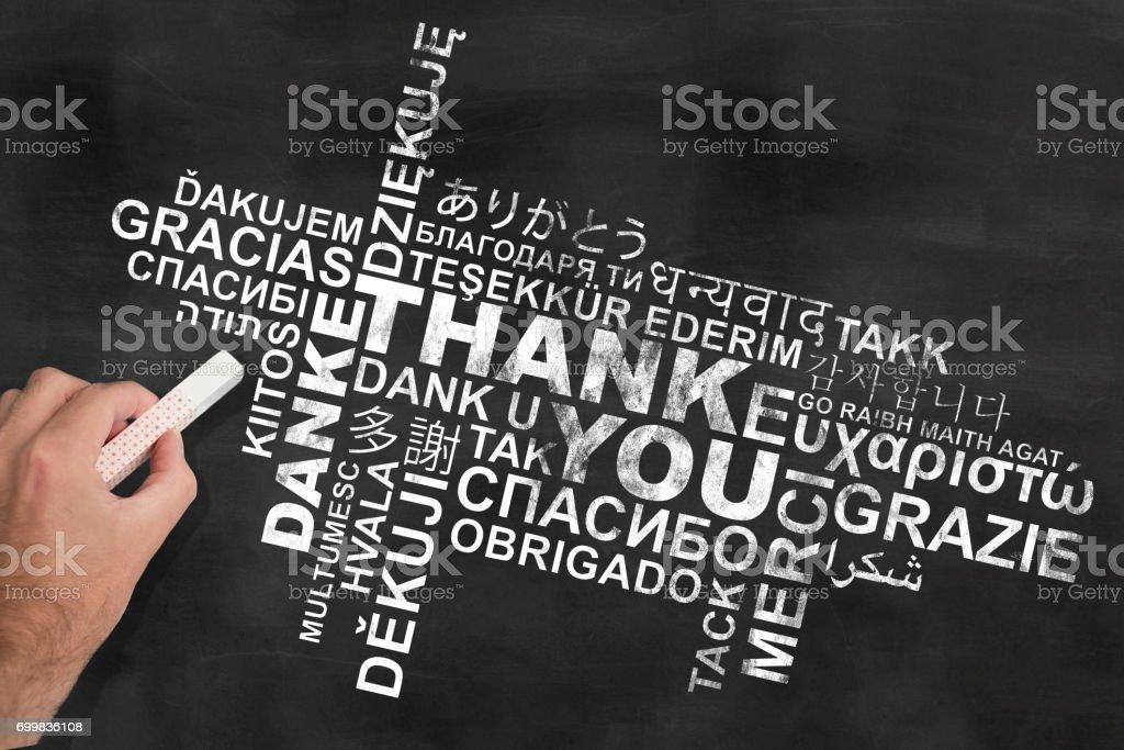 Hand mit einem Stück Kreide schreiben danke in verschiedenen Sprachen an Tafel-Tafel – Foto