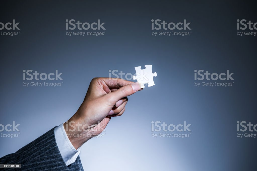 hand holding a piece of jigsaw puzzle, business to business, business matching concept stock photo
