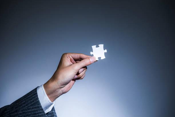 hand mit einem stück von jigsaw puzzle, business to business matching-konzept - dinge die zusammenpassen stock-fotos und bilder