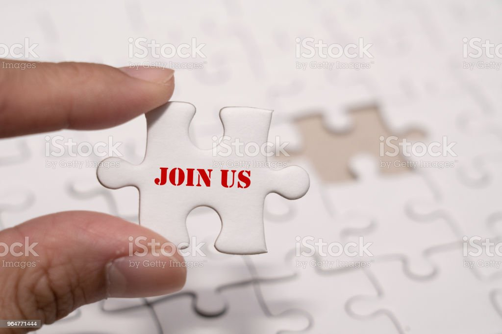 Hand holding a piece of join us wording jigsaw puzzle for human resource recruitment concept royalty-free stock photo