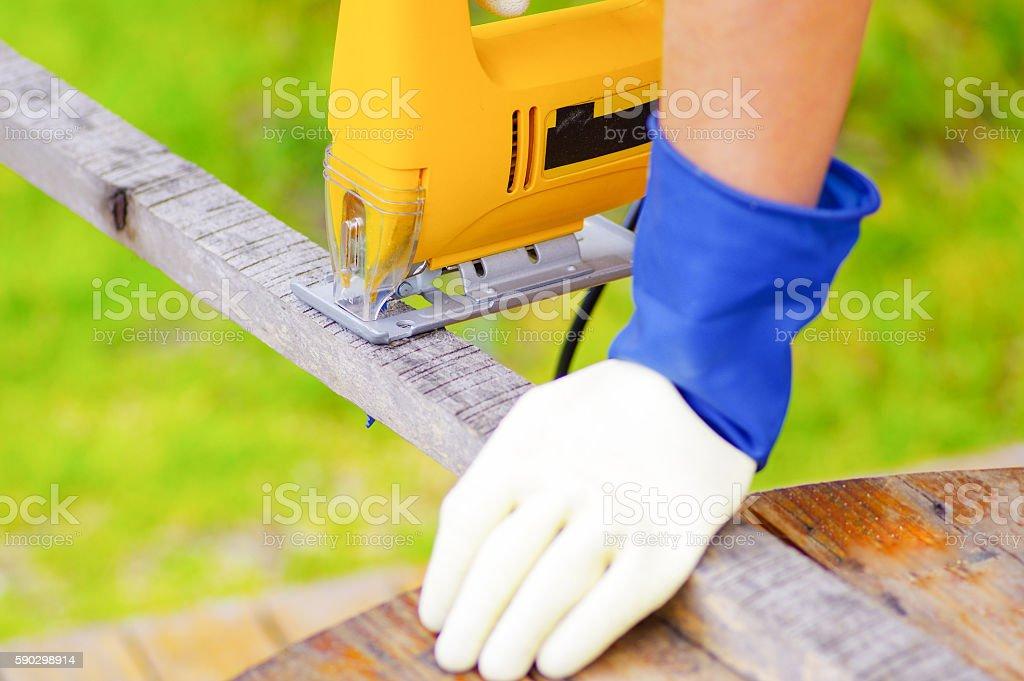 hand holding a piece of wood while the electric jigsaw royaltyfri bildbanksbilder
