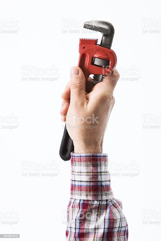 Hand holding a pipe wrench stock photo