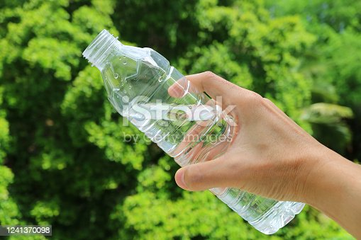 Hand holding a plastic bottle of drinking water against green foliage
