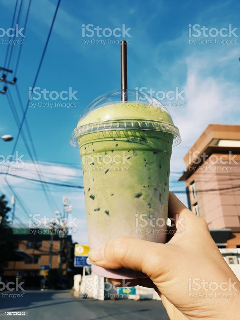 Hand holding a plastic cup of iced green tea stock photo