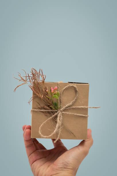hand, die ein geschenk, geschenk-box-rustikalen stil auf blauem hintergrund - eco bastelarbeiten stock-fotos und bilder