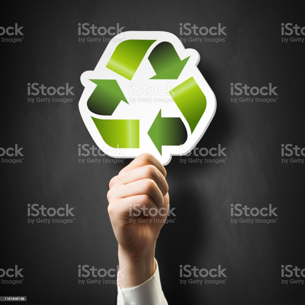 hand holding a recycling symbol in front of a blackboard