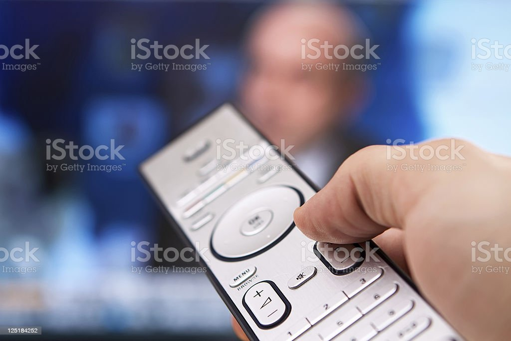 Hand holding a remote as a TV plays in the background stock photo