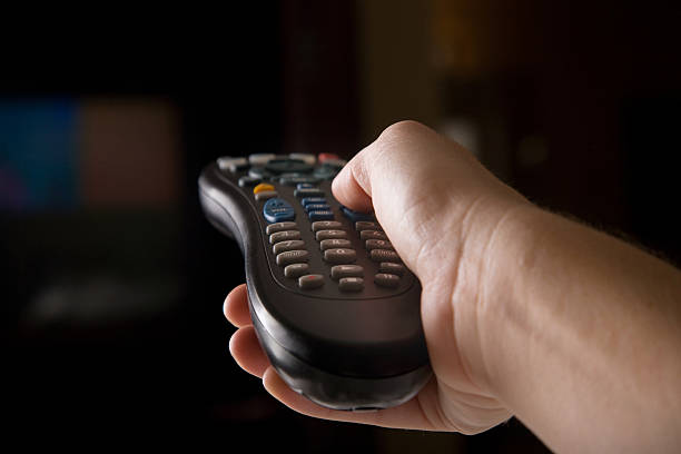 A hand holding a remote to change channels A hand pointing the remote towards the hint of a television in a dark background. cable tv stock pictures, royalty-free photos & images
