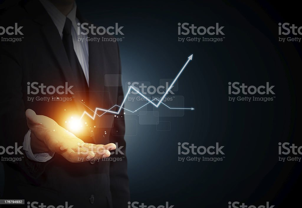 Hand holding a rising arrow stock photo