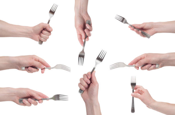 hand holding a silver fork on an isolated white background. Multiple image. hand holding a silver fork on an isolated white background. Multiple image. fork stock pictures, royalty-free photos & images