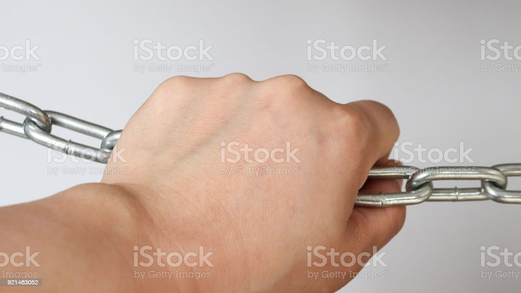 A hand holding a silver metal chain stock photo
