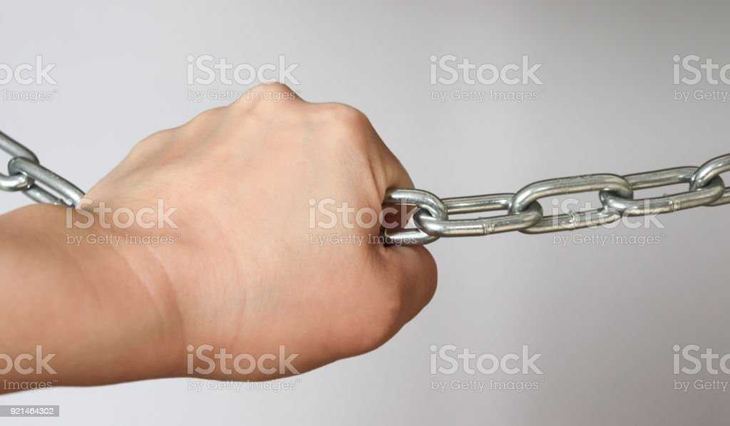 A hand holding a silver metal chain strong stock photo