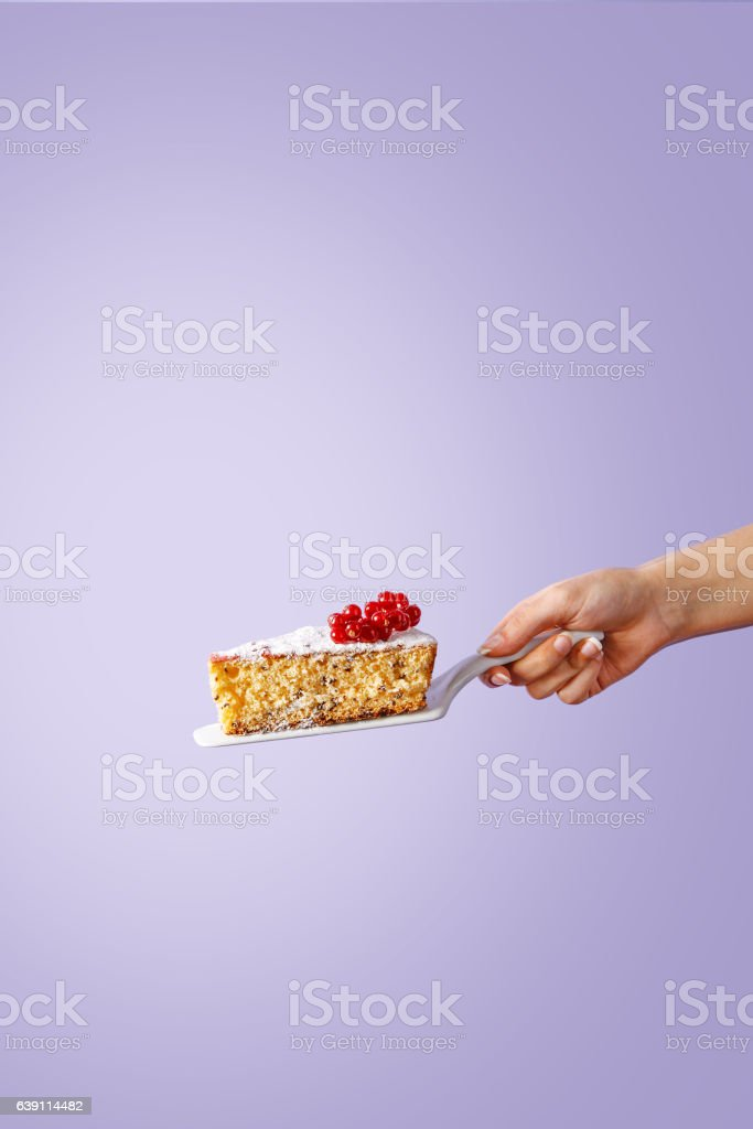 Hand holding a slice of sponge cake on violet background stock photo