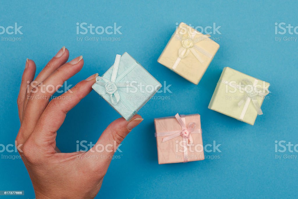 hand holding a small gift box on blue background stock photo