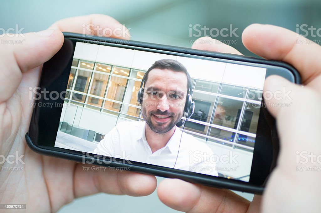 hand holding a smart phone during a skype video stock photo
