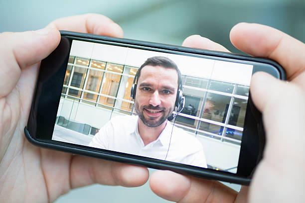 Mano sosteniendo un teléfono inteligente durante un vídeo de skype - foto de stock