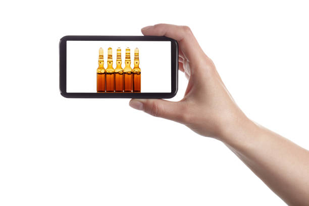 Hand holding a smart phone with medical glass ampoules on screen stock photo