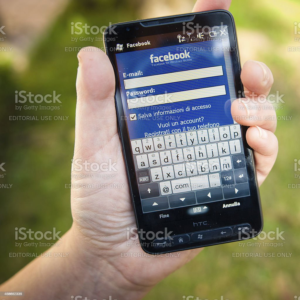 Hand holding a smarthphone with facebook.com apps royalty-free stock photo
