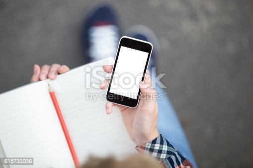 istock Hand holding a smartphone against a copybook with a pencil 615733036